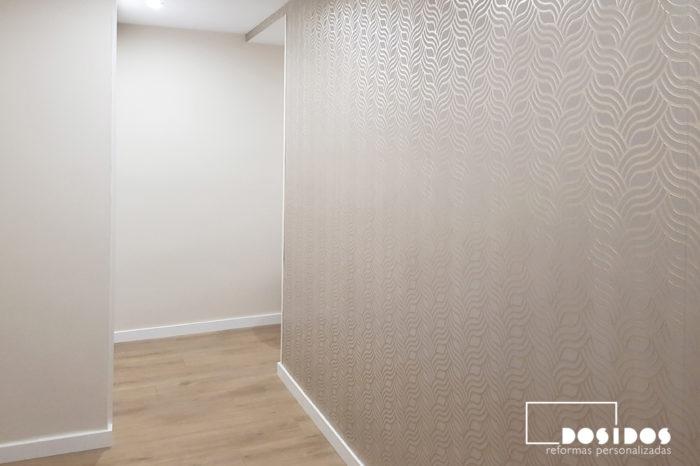 recibidor con parquet y una pared con papel pintado geométrico en color dorado