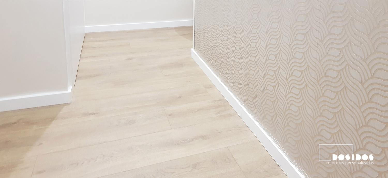foto panorámica de un recibidor con suelo de parquet y una pared con papel pintado dorado geométrico