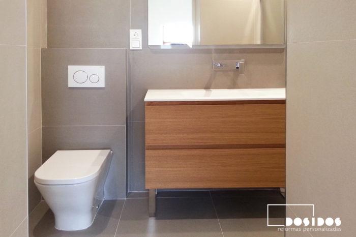 Reforma de baño con inodoro empotrado y mueble de madera con 2 cajones y patas cromadas.