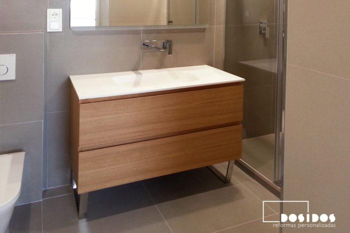 Reforma baño moderno con mueble de madera, lavabo de krion y grifo empotrado a pared.