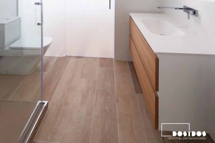 Reforma de baño moderno, blanco con suelo imitación a madera, mueble de baño con 2 cajones.
