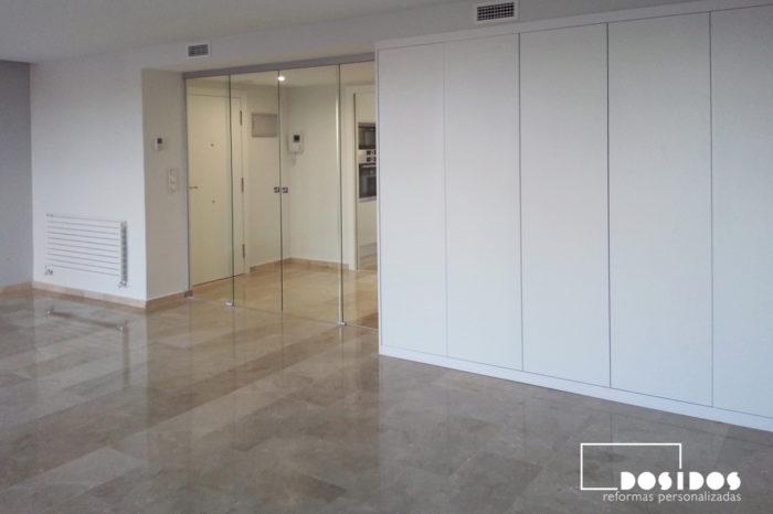 Gran salón con puerta doble de cristal transparente corredera, suelo de mármol pulido y armario de almacenaje.