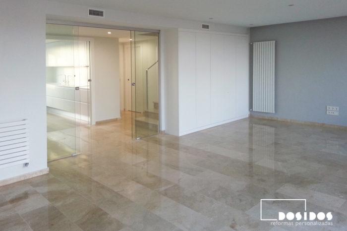 Gran salón con puerta corredera de cristal transparente, suelo de mármol pulido, armario lacado y radiador diseño vertical.