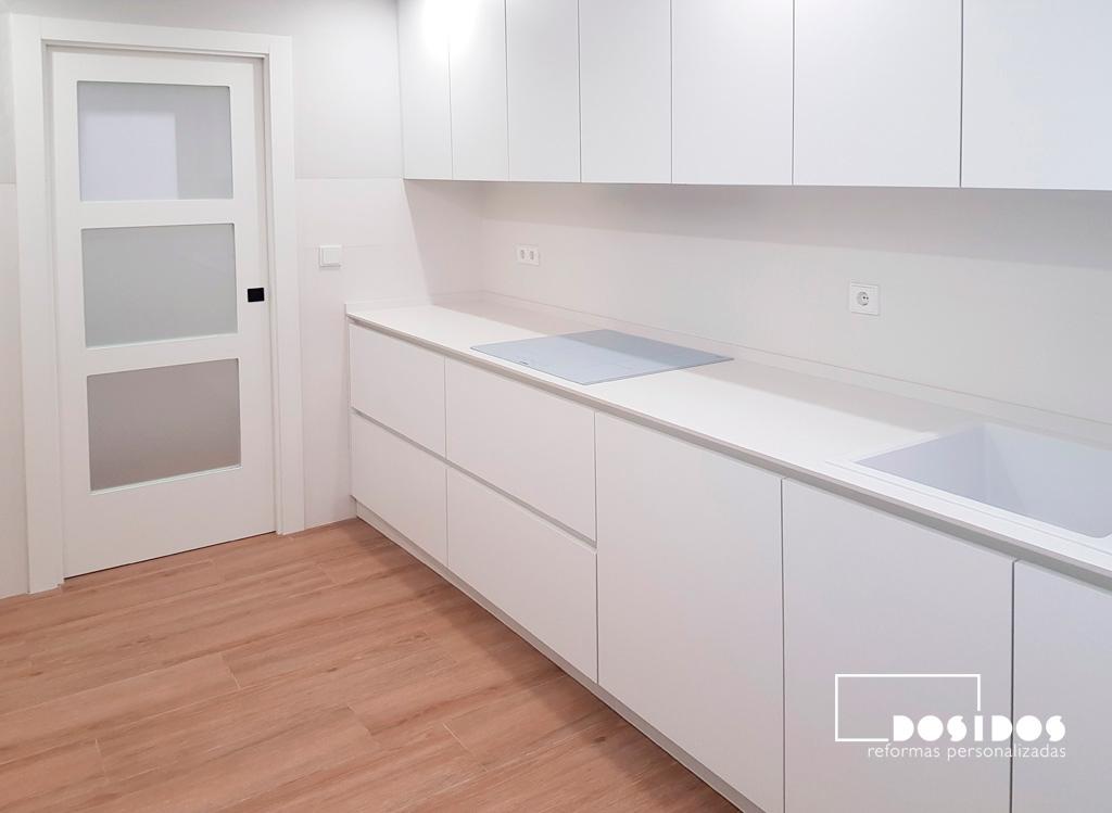 Cocina con muebles y puerta blanco, suelo de madera